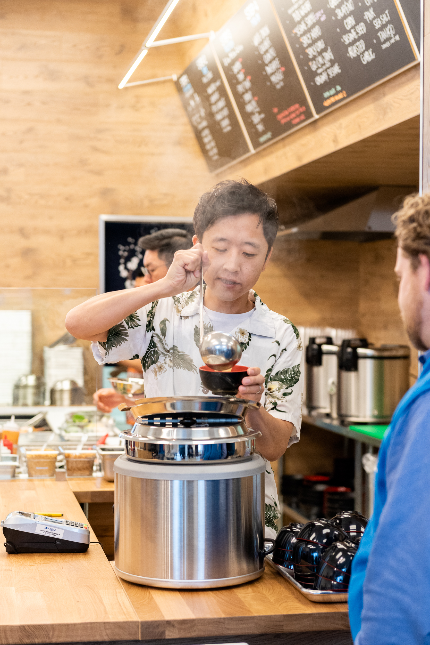 Joy Poke owner Justin Hwang serves steaming miso soup to a customer